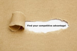 Find your competitive advantage! appearing behind torn brown paper.